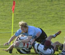 University flanker Sam Dickson crashes over the line in the tackle of Southern backs Tom Yarrall ...