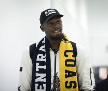 Usain Bolt, draped in a Central Coast Mariners scarf, arriving in Sydney today. Photo: Getty Images