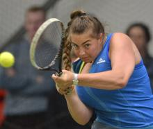 Defending champion Megan Rogers, of Auckland, plays a backhand against Otago's Libby Scott during...