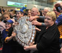 Fans clutch the shield at Dunedin Airport yesterday. Photos: Gregor Richardson