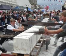 Competitors take part in the men's doubles Oamaru stone-sawing championship at the Victorian fete...