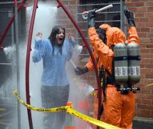 An actor experiences a decontamination shower during an emergency exercise at the Dunedin Medical...