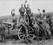 A cheery group of our boys on a captured German 4.2 inch gun taken during the British advance in...
