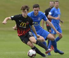 Canterbury United's Seth Clark is in possession of the ball as Southern United's Tony Whitehead...