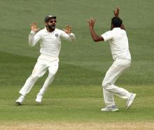 India's Virat Kohli (L) and Ravi Ashwin celebrate their victory at the fall of the final...
