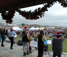 A band (left) plays festive tunes at Christmas at the Harbour in Oamaru yesterday. Photos: Daniel...