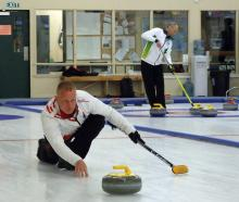 Danish curler Kasper Wiksten follows through during a practice run on the first day of the world...