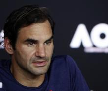 Switzerland's Roger Federer speaks duriong a news conference after losing the match against...