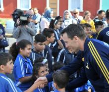 Ben Smith shakes a noy's hand as he arrives with the Highlanders at the Al Huda mosque in Dunedin...