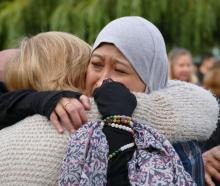 Maznab Abu Assan is embraced by Christine Adams, both of Queenstown, at the end of a candlelight...