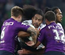 Bunty Afoa hits the ball up for the Warriors as Cameron Munster and Kenny Bromwich tackle him...
