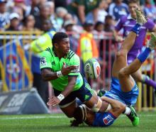 Highlanders winger Waisake Naholo gets a pass away as he istackled by his Stormers counterpart,...