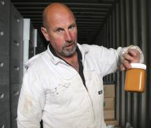 Southland beekeeper Murray Christensen holds a jar of his own ready-to-sell Southern Hills Honey....