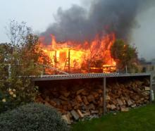 A house is consumed by flames in Riverside Village,  Glenavy, yesterday. PHOTO: SUPPLIED