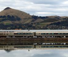 Dunedin's Silver Fern rail car crosses the causeway at Blanket Bay, with Otago Peninsula's...