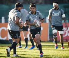 Otago and Highlanders first five-eighth Josh Ioane runs with the ball past Ofa Tuungafasi (left)...