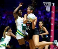 Silver Ferns' goal attack Ameliaranne Ekenasio looks to pass around ZImbabwe's Adelaide Muskwe in...