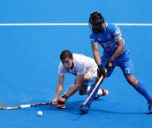 Black Sticks forward Jacob Smith (left) competes for the ball with India defender Harmanpreet...