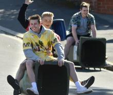 Young party-goers ride down Union St on a wheelie bin before Dunedin police arrived to put an end...