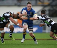 Otago flanker Slade McDowall tries to get between loose forward Marino Mikaele-Tu'u (left) and...