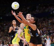 Ameliaranne Ekenasio of the Silver Ferns reaches for the ball under pressure from Courtney Bruce...