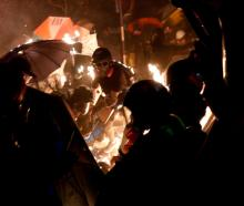 Anti-government protesters take cover during a standoff with riot police at the Chinese...