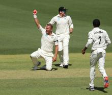 Neil Wagner of New Zealand celebrates after taking a catch off his own bowling to dismiss David...