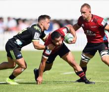 Fasi Fuatai of the Crusaders is tackled by Wes Goosen of the Hurricanes during the Super Rugby...