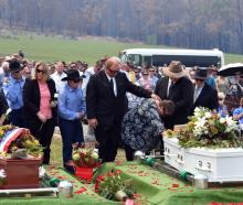Janelle Salway (R) grieves during the funeral in Cobargo yesterday of her son Patrick and husband...