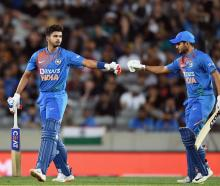 India's Shreyas Iyer (L) and Manish Pandey bump fists during the match against New Zealand. Photo...