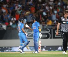 Indian batsmen Shreyas Iyer (L) and KL Rahul celebrate while Blair Tickner walks back to his mark...