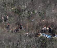 Investigators work at the scene of the helicopter crash which killed NBA star Kobe Bryant in...