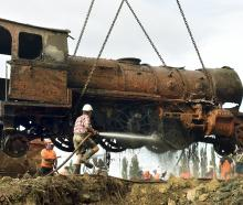 Project Steam member Clark McCarthy, of Dunedin, hoses mud off a steam locomotive as it is...