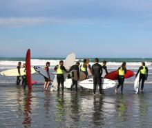 Farmers check out the waves with a surfing instructor before heading out for a lesson. Photo: RNZ...