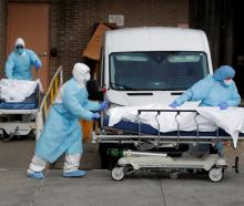 Healthcare workers wheel the bodies of deceased people from the Wyckoff Heights Medical Center...