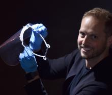 Damien van Brandenburg, of Architecture Van Brandenburg, holds one of the masks he made on a 3-D...
