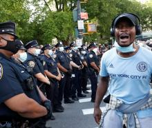 A protester stands next to police officers during a rally in New York against the death of George...