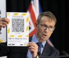 Dr Ashley Bloomfield holds up an example of a QR code that can be scanned by the recently...