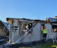 Fire fighters inspect the house that burnt in Queenstown. Photo: Matthew McKew