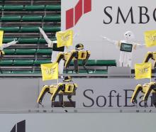 Robots cheer the team next to empty spectator seats at a baseball game between SoftBank Hawks and...