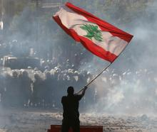 A demonstrator waves the Lebanese flag in front of riot police during the protest in Beirut....