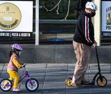 A young child and man wearing masks are seen riding a bicycle and scooter in Melbourne. Photo:...