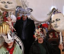 Trying on masks ahead of the Midwinter Night's Dream street party are (from left) Oamaru artist...