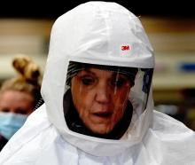 Nurse Deb Grabo, wearing a powered air purifying respirator hood, prepares to begin her shift at...