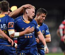 Slade McDowall (centre) celebrates with his Otago teammates after their win against Canterbury...