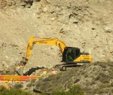 An excavator works to clear debris from the base of the slip that loomed over State Highway 8 in...