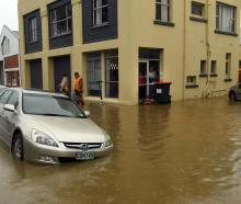Harrow St buildings are sandbagged after a water main in Leith St burst yesterday. PHOTOS:...