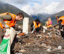 Cleaners picking up rubbish that spilled out of the old Fox landfill. Photo: Owen Kilgour via RNZ