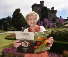 Larnach Castle owner Margaret Barker holds a copy of British magazine Country Life which features...