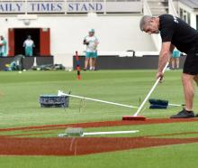 Peter Ryder, of Williams Signs and Graphix, paints a logo on the ground surface in preparation...